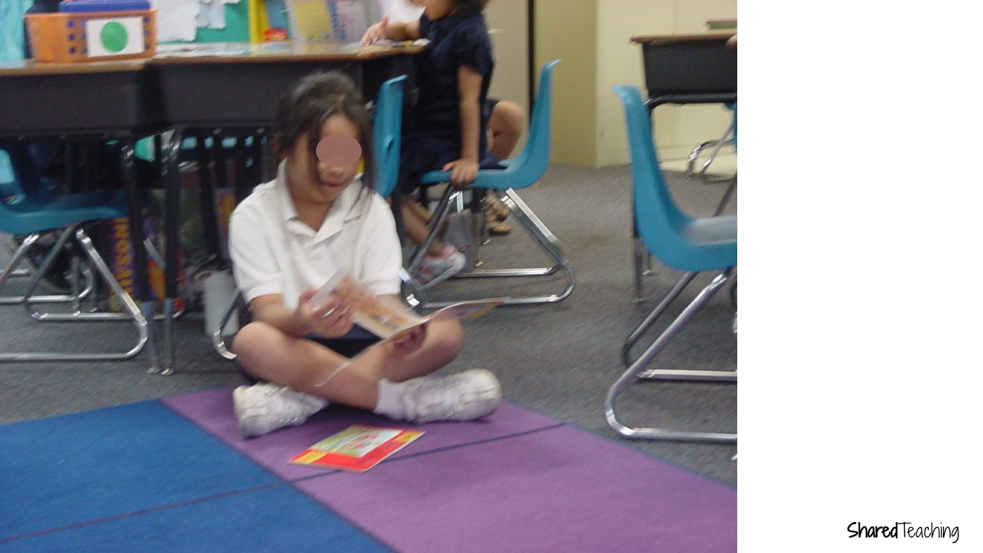 A student reads books she chose from the classroom library during centers time.